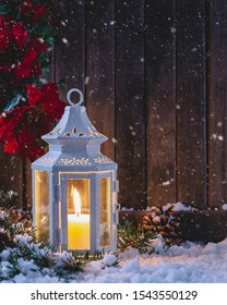 Snowy holiday night scene with glowing lantern on a rustic wooden background with copy space