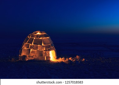 A snowy house called an igloo at sunset.