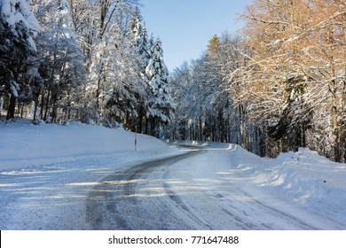 A snowy and icy road curve in the Vosges mountains (France) in winter - december 2017 - horizontal