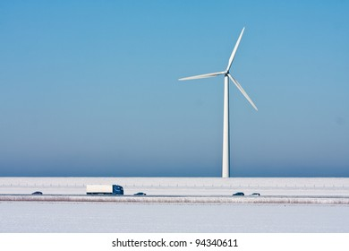 Snowy landscape with a big windturbine and a highway in front of it