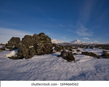 A snowy lava field in Iceland with a big lava rock