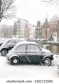 Snowy little car on the bridge in the city center Amsterdam Netherlands. Blizzard on winter in the Netherlands. Small car covered with snow on a bridge. Snowfall in capital Netherlands