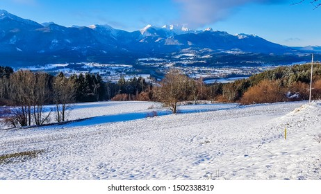 A snowy mountain landscape. Beautiful and sunny winter day, lots of snow everywhere. Bare branches of trees. Winter wonderland. Winter playground. The peaks of the mountains covered with snow.