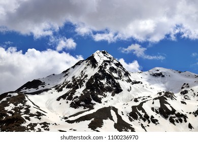 Snowy Mountain Peak on Blue Ski and White Clouds