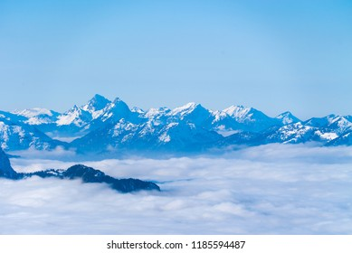 Snowy mountain range reaching above cloudy valley in the Bavarian alps