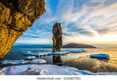 Snowy mountain sea bay sunset sea rock landscape. Sunset sea rock in sea bay panorama. Sunset snow sea rock sunset view