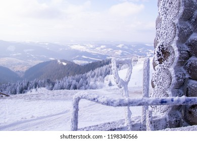 Snowy mountain top at a ski resort and snow-covered sweeping equipment