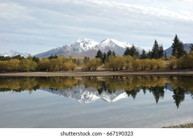 snowy mountain and trees mirroring in a lake