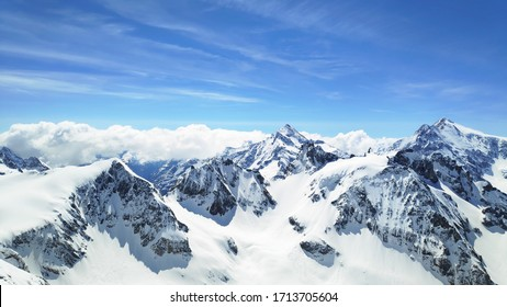 Snowy mountains covered in clouds beautified by the sky - Shutterstock ID 1713705604