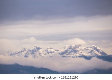 Snowy mountains emerging from the clouds