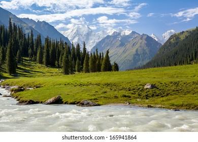Snowy mountains peak and Karakol river. Tien Shan, Kyrgyzstan