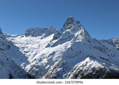 Snowy Mountains peaks in the blue sky Caucasus