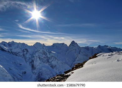 Snowy Mountains peaks in the clouds blue sky Caucasus
