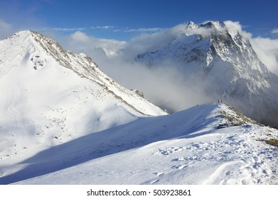 Snowy mountains peaks with mist and two hikers on top at sunny day.