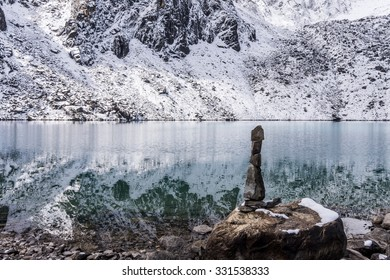 Snowy mountains reflecting in emerald water of the second Gokyo lake (Taujung Tsho), Everest region, Nepal. A stone stack in the foreground