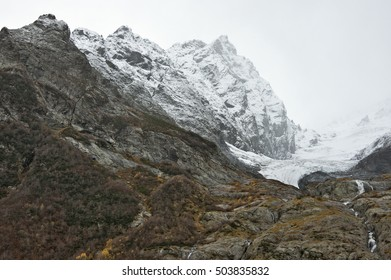 Snowy mountains tops in mist.