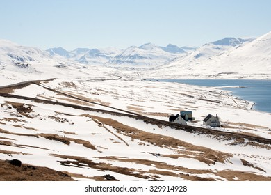 Snowy northern landscape with mountains and little farm houses. Iceland.