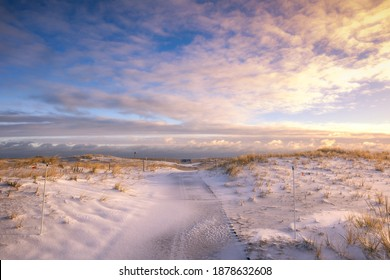 Snowy path leading to the beach under golden light. Robert Moses State Park - Fire Island New york