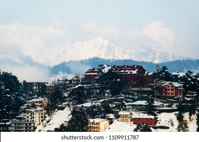 the snowy peak in shimla with small colorful houses covering in snow during winter