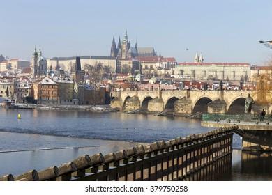 Snowy Prague Lesser Town with gothic Castle and Charles Bridge, Czech Republic