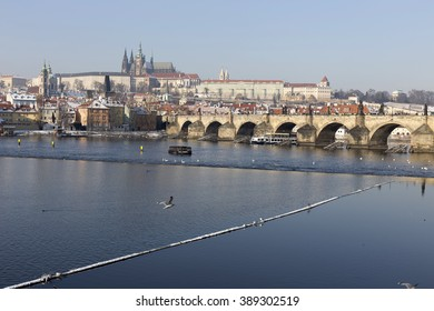 Snowy Prague Lesser Town with gothic Castle and Charles Bridge in the sunny Day, Czech Republic