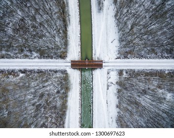 A snowy river and a bridge in winter with a forest