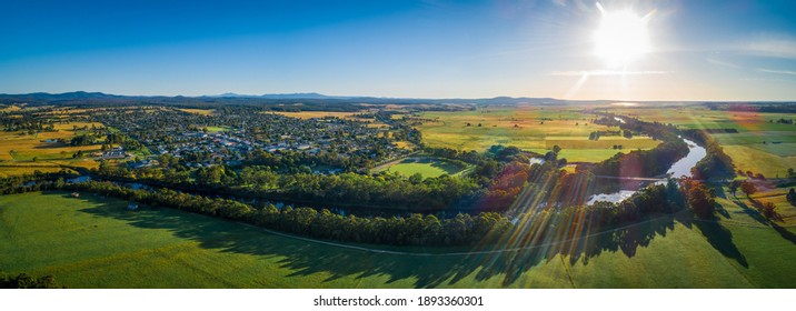 Snowy River meanders around small rural town and meadows at sunset - aerial panoramic landscape