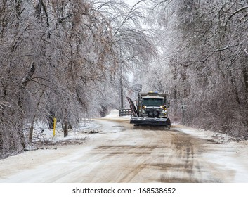 A snowy road being plowed in winter.
