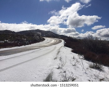 Snowy road with black mountains and clouds