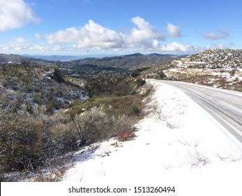 snowy road into sparsely populated valley
