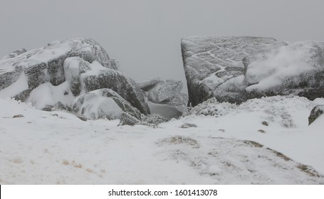 Snowy rocks in Serra da Estrela Natural Park on a day with tough conditions - fog, wind and snow