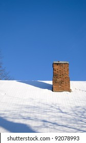 Snowy roof and red brick chimney in background of blue sky