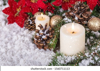 Snowy scene of burning candles and holiday decor with copy space