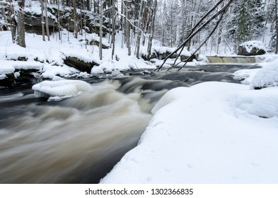 Snowy scene by the Nommeveski waterfall (cascade) on the river Valgejogi in Lahemaa National Park, Estonia in wintertime. Long exposure brings good motion effect to the river.