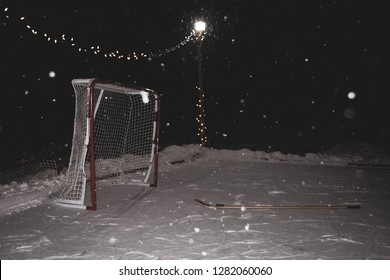 A snowy scene of a hockey net, stick and puck on the ice.