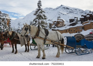 A snowy scene in the ski resort of Avoriaz where horses wait to transport people on their sleighs.