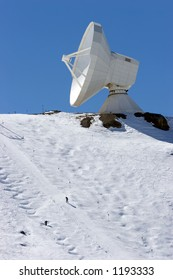 Snowy ski slopes of Pradollano ski resort in the Sierra Nevada mountains in Spain with large telescope and observatory