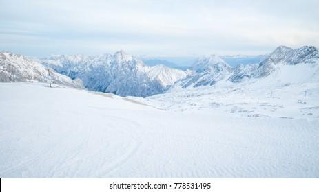 Snowy slope between alpine peaks