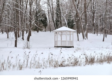 Snowy summerhouse in winter. Empty urban park during snowfall. Scenic view of the lonely arbor in the winter city
