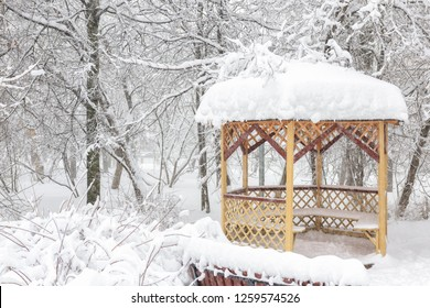 Snowy summerhouse in winter, Moscow, Russia. Empty urban park during snowfall. Scenic view of the lonely arbor in the winter city.
