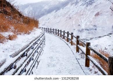 Snowy walkway with wooden fence to go to the Jigokudani hell valley, Noboribetsu, Hokkaido, Japan