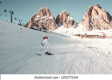 Snowy white winter day in high mountains. Woman in fashionable jacket with fur, ski goggles and helmet. Girl skiing.