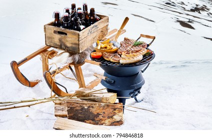 Snowy winter barbecue outdoors in the cold with a crate of beer bottles on a sled and spicy sausages and T-bone steaks grilling on a portable BBQ