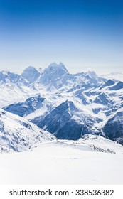 Snowy winter Greater Caucasus mountains with Ushba at sunny day, view from ski slope Elbrus. Kabardino-Balkaria, Russia