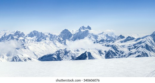 Snowy winter Greater Caucasus mountains (Ushba, Kogutai and other) at sunny day. Panorama view from ski slope Elbrus, Kabardino-Balkaria, Russia
