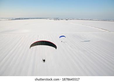 Paysage hivernal neigeux au ciel bleu vu du ciel. Deux parapentistes motorisés survolent les champs blancs