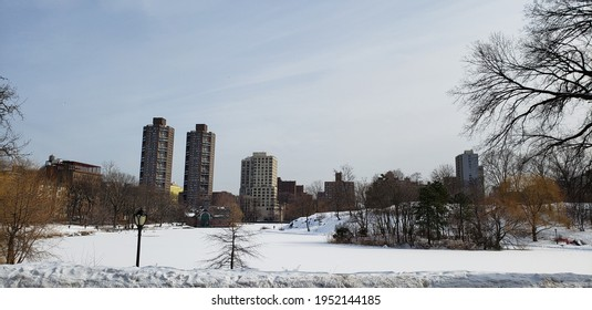 Snowy, winter landscape of northern Central Park in Manhattan looking over the frozen Harlem Meer with skyscrapers in the background. - Shutterstock ID 1952144185