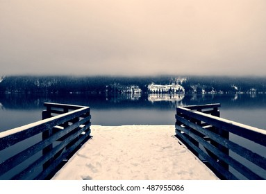 Snowy winter landscape on the lake in black and white. Monochrome image filtered in retro, vintage style with soft focus, red filter and some noise; high contrast. Lake Bohinj, Slovenia.