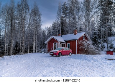 Snowy winter landscape with a one-story house in the forest and a red car in front of him