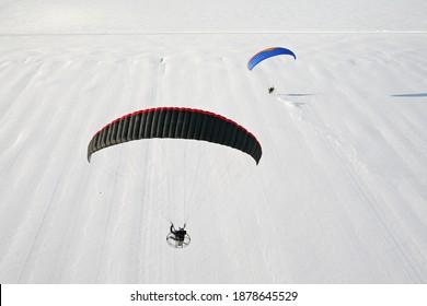 Paysage hivernal neige vu du ciel. Deux paramoteurs survolent les champs blancs